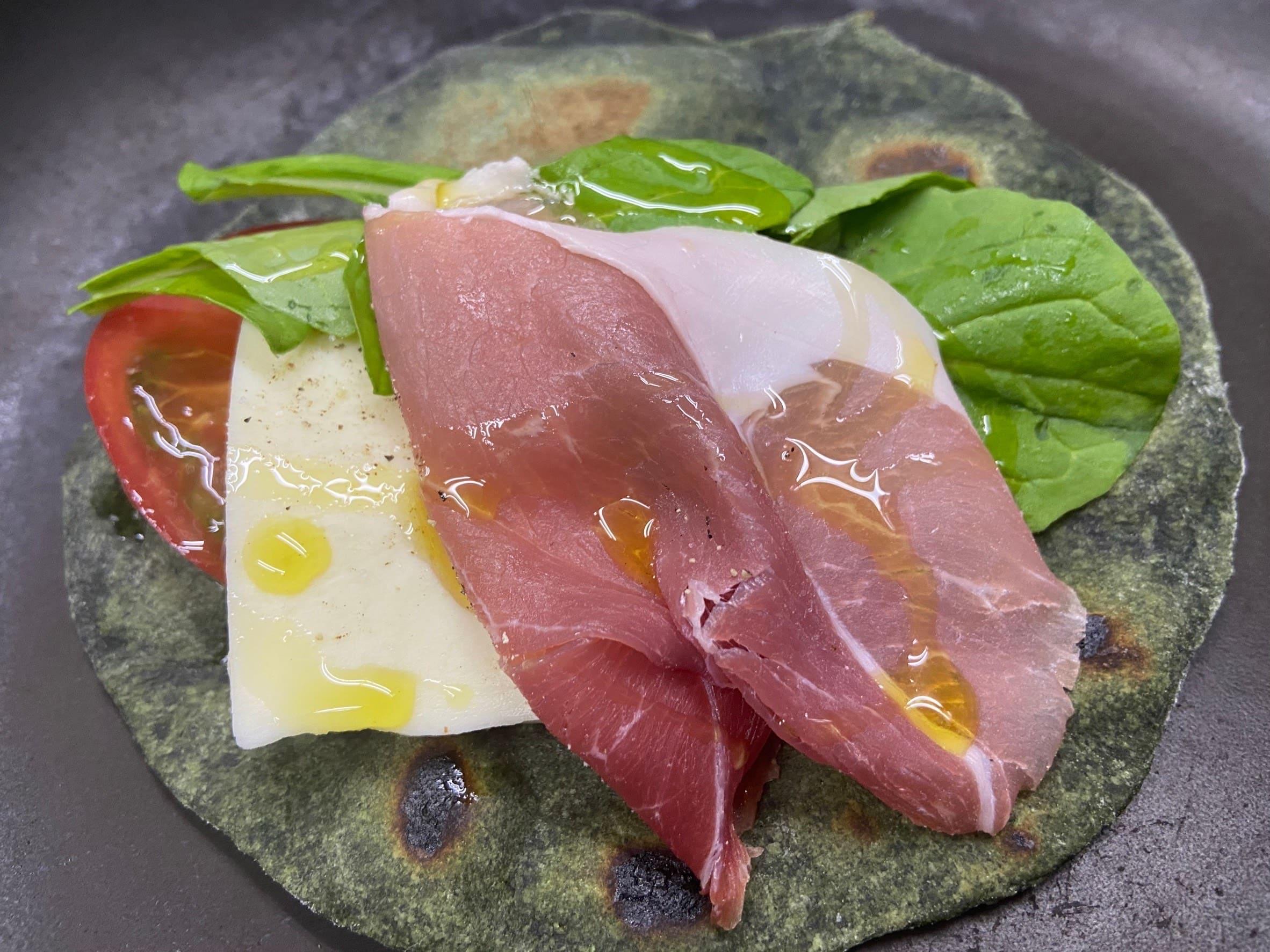 よもぎを練り込んだ平たいパンを香ばしく焼きあげ、生ハム、トマト モッツァレラチーズ、ルーコラを挟んだパニーニです。